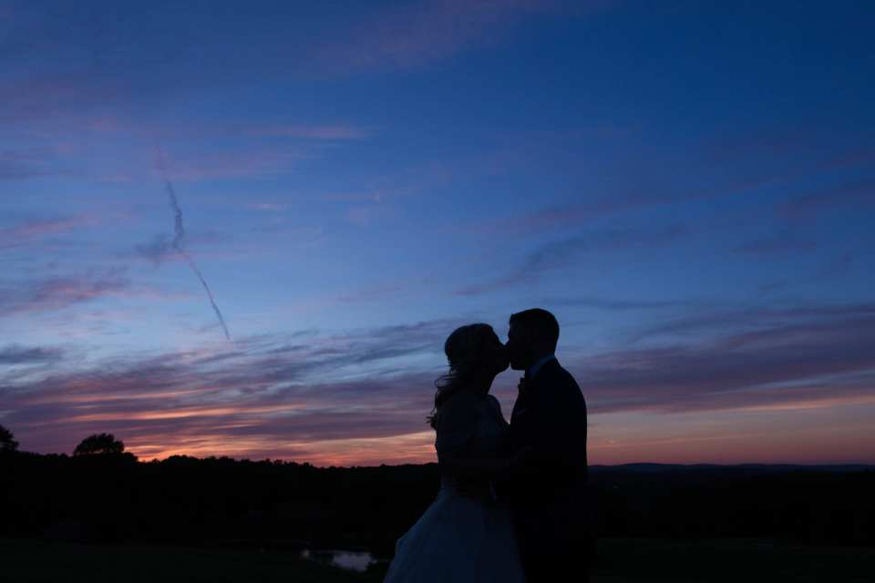 the bride and groom kissing in silhouette in front of a gorgeous blue and orange sunset