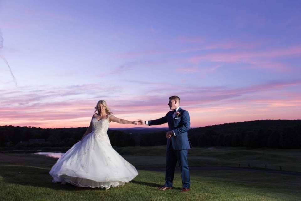 the bride and groom twirling about during portraits in front of a gorgeous purple, pink and blue sunset at the Skyview Golf Club