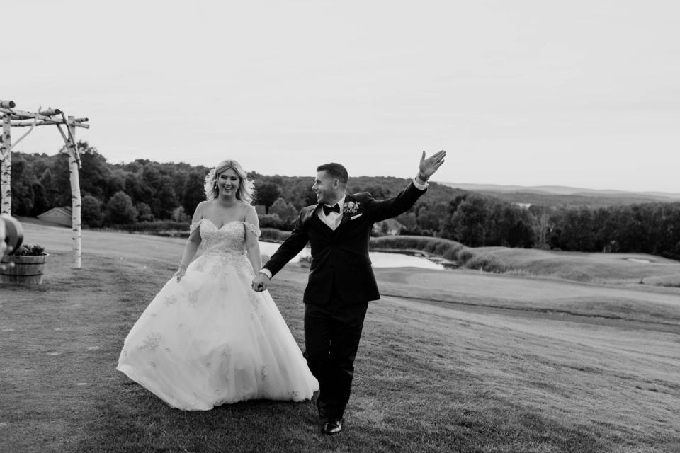 black and white photo of the bride and groom smiling and laughing while holding hands during their portraits at the Skyview Golf Club