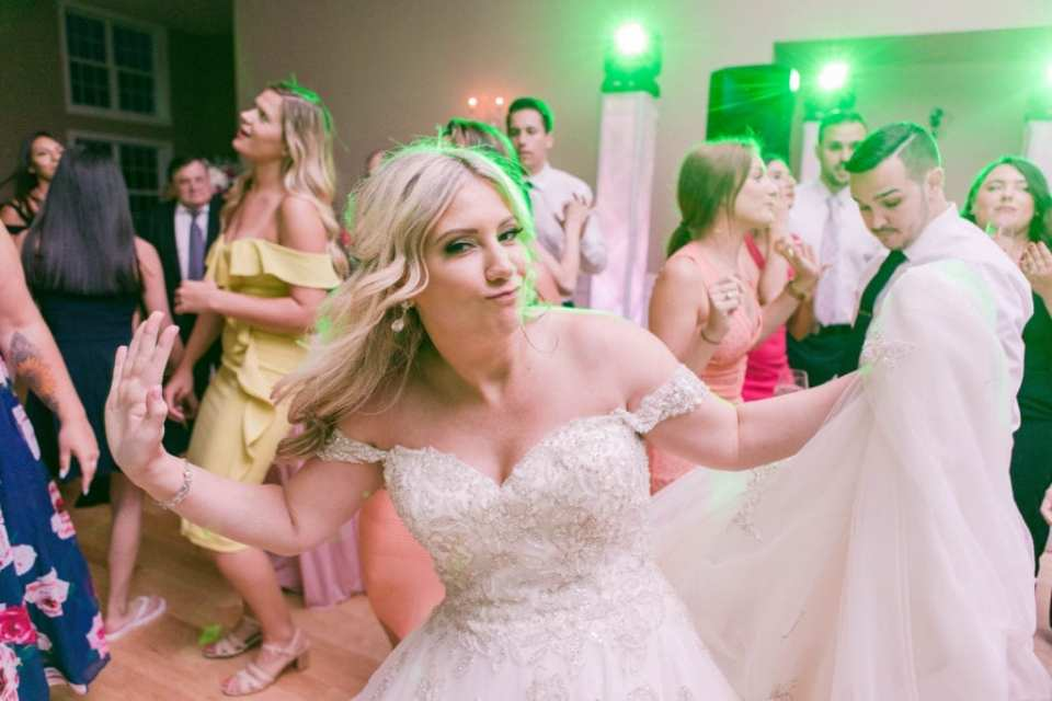 the bride holds the train of her Justin Alexander gown while dancing during the reception