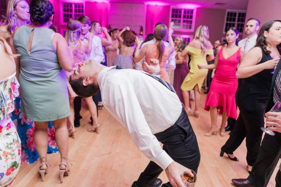 a male guest does a back arch while dancing during the reception