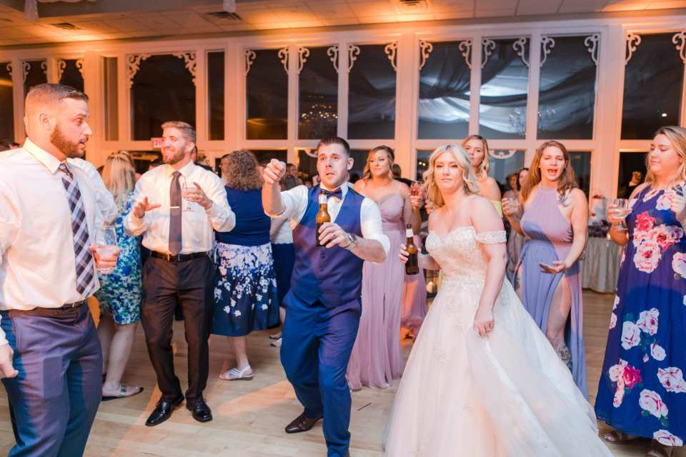 the bride and groom dance during the reception at the Skyview Golf Club with beers in their hands