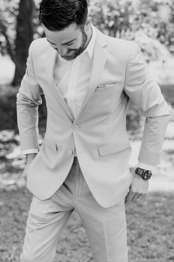 black and white photo of groom candidly laughing and being comfy in his tieless suit
