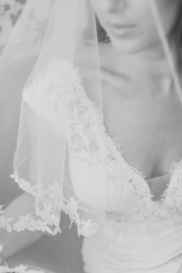black and white image of the details of the brides lace gown under the veil, only her nose and lips and chin appear