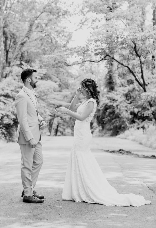 a black and white full length photo of the bride and groom during their first look. The bride wiping away a tear as they smile at one another.