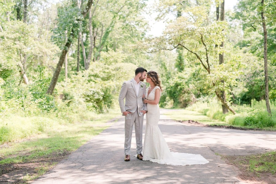 Wide angle portrait of the bride and groom in the woods on the property of the Mountain Lakes House. They are standing side by side, she has her hands wrapped around his left bicep, they have their noses touching. Her white lace v-neck gown is by Calla Blanche, his light grey suit by Generation Tux