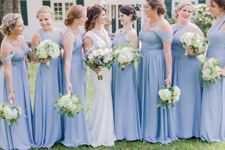 Informal photo of the bridal party with the bride, each chatting with one another, holding their bouquets at different heights. Bridesmaids in dusty blue gowns by Azazie