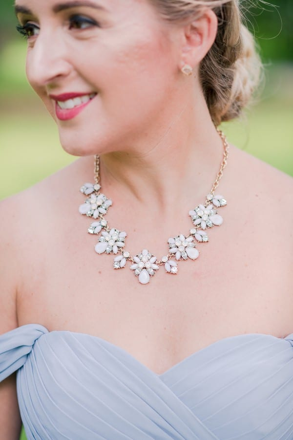 Close up of a member of the bridal party's necklace. Bunches of flowrs made of pastel enamels strung along on a gold chain