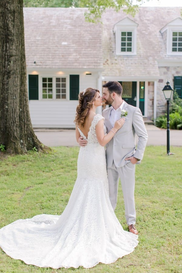 full size photo of the bride and groom from behind the bride, showing the entire back of her Calla Blanche white lace brial gown, her right arm on his chest, his left arm in his pocket. His light grey suit by Generation Tux. Photo in front of the Mountain Lakes House in Princeton, NJ