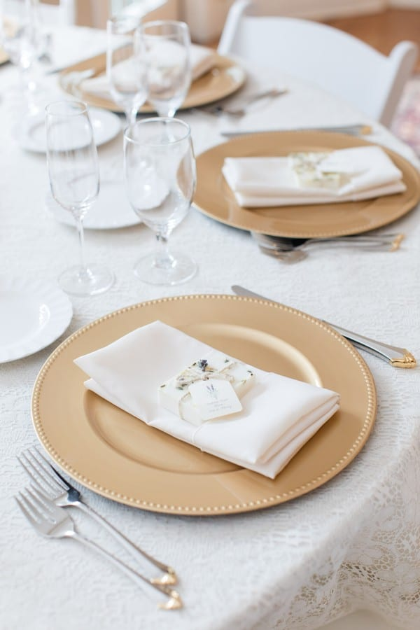 Wedding details: a gold charger on white lace linens on a table during the reception with a personalized favor box on top of a white napkin