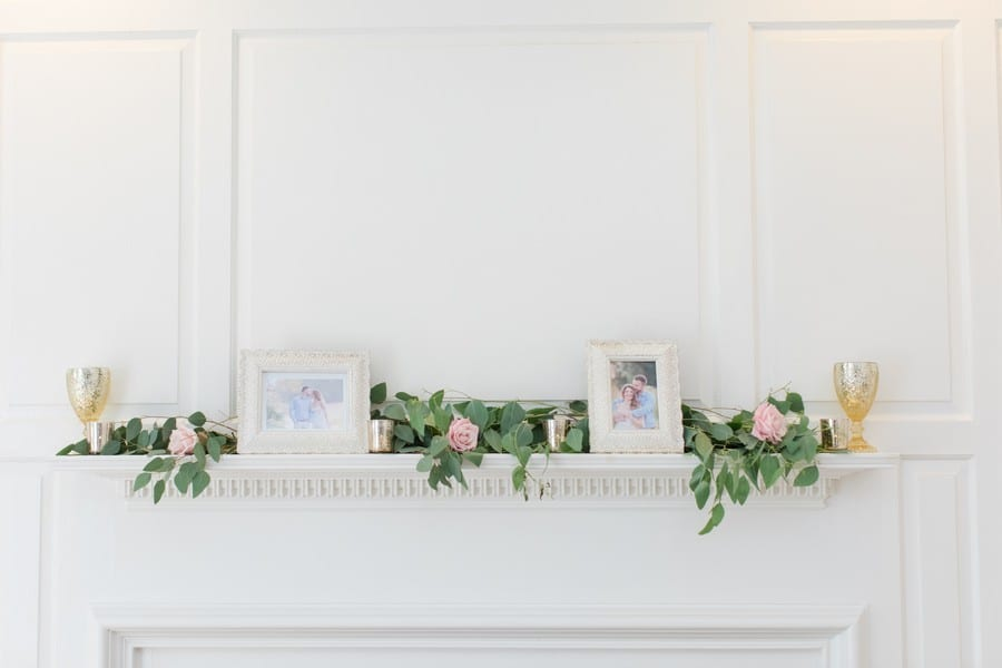 Wedding details: a fireplace manted decorated with pink flowers, greens and the engagement photos of the bride and groom
