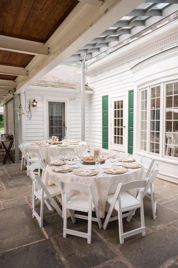 Reception table outside of white wooden folding chairs and white linens of the Mountain Lakes House in Princeton, NJ