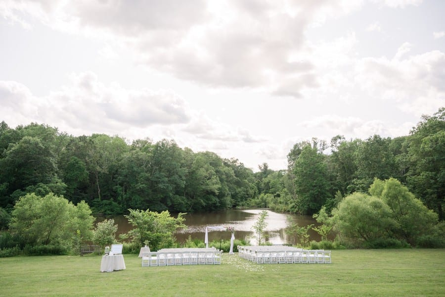 Wide angle shot of the ceremony location in front of the lake at the Mountain Lakes House in Princeton, NJ. The ceremony arch of wood, decorated in wrapped white chiffon, with a floral arrangement on the top left corner of pink and ivory florals and greens, with coordinating aisle decor