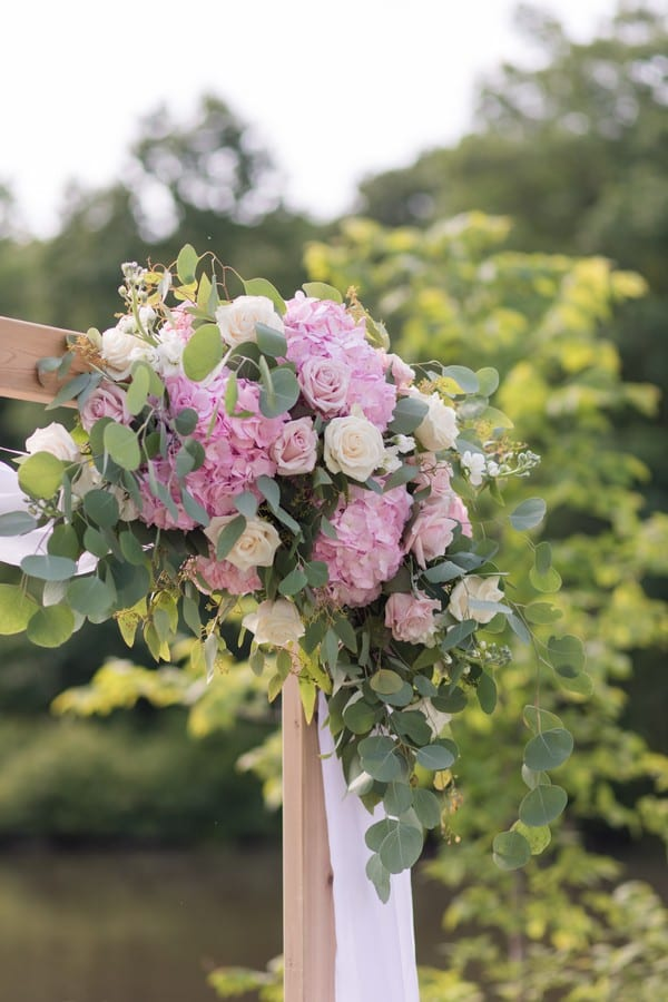 Wedding details: the ceremony arch floral arrangement is decorated in pink florals with a few cream roses here and there, with greens galore, by Monday Morning Flowers
