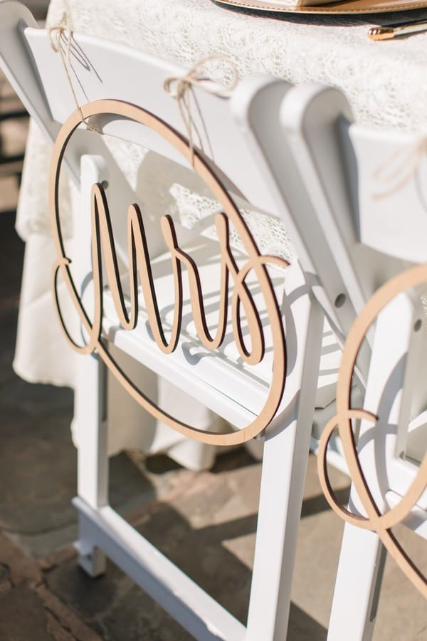 Wedding details: a wooden round Mrs. sign hanging on the brides white wooden folding hair
