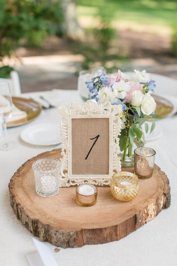 Details of the wedding: A reception table centerpiece made of a wood slice with various types of votives and small candles on it, as wel as a small vase of light pink, light blue, and white flowers. The table number is on burlap, ramed in a coordinating frame