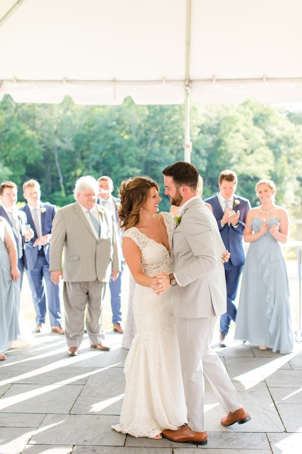 full length photo of the bride The bride in a mermaid style lace v-neck gown by Calla Blanche with her groom in a grey suit during their first dance