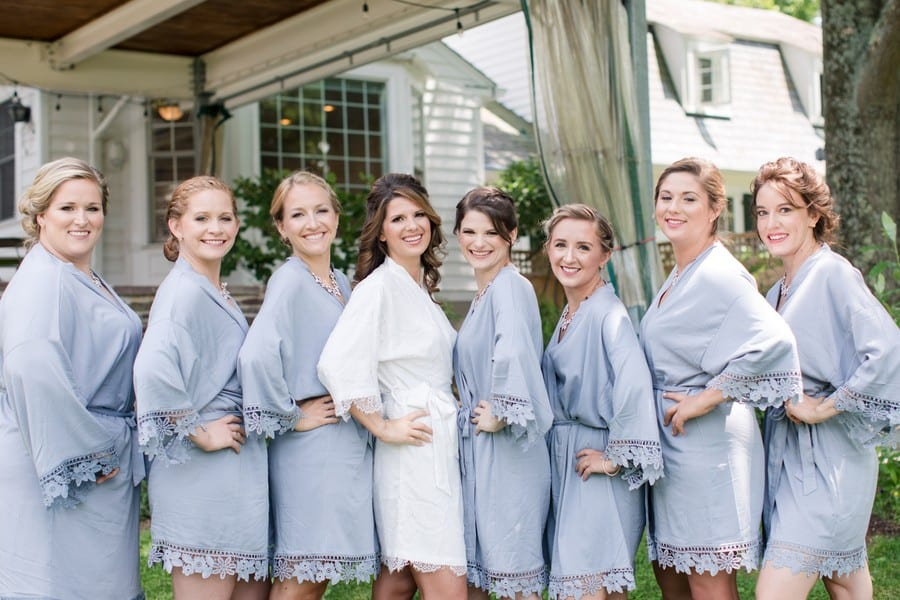 the bride and her bridal party in short robes; the bride in white, the bridal party in pale blue