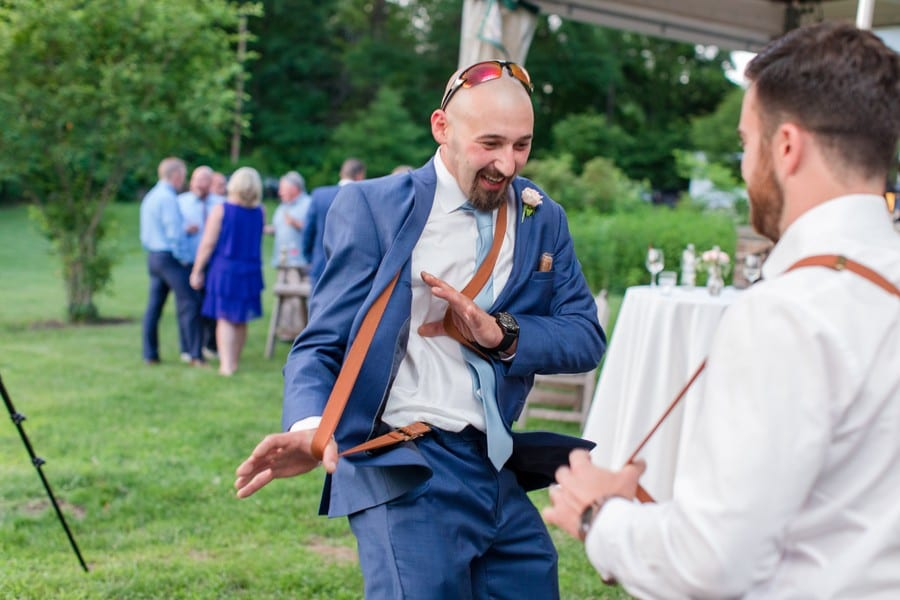 Member of the wedding party in blue suit and light blue tie with brown belt suspenders dances during the wedding reception