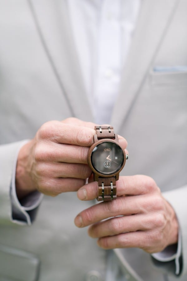 Groom showing off his grooms gift a watch from Jord Watches