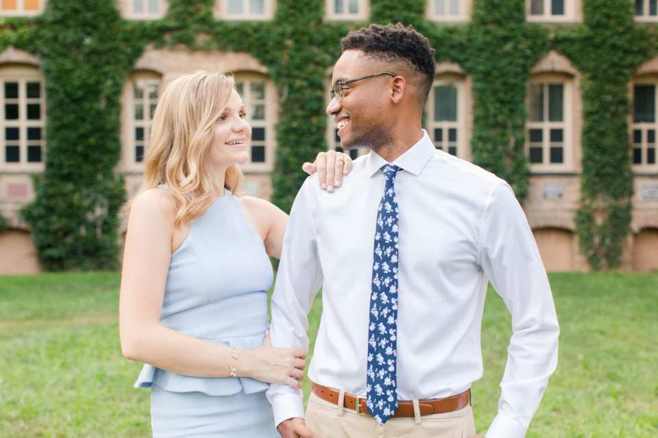 Engaged couple, she to his right, with her left hand on his shoulder, right hand holding his arm, on the campus of Princeton University. She is wearing a pale blue peplum dress by John Paul Ataker from Castle Couture. He is wearing a shirt by Calvin Klein, pants by Old Navy, tie from Bar III