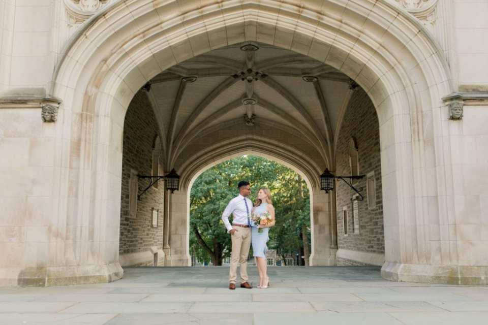 engaged couple standing next to each other, looking at one another, in front of Blair Hall on the campus of Princeton University a floral bouquet of peaches, blues and whites by Magnolia West Events in her hand. Bride to be in a light blue sleeveless peplum dress from Castle Couture by John Paul Ataker, he in a shirt by Calvin Klein, tie by Bar III, pants by Old Navy.