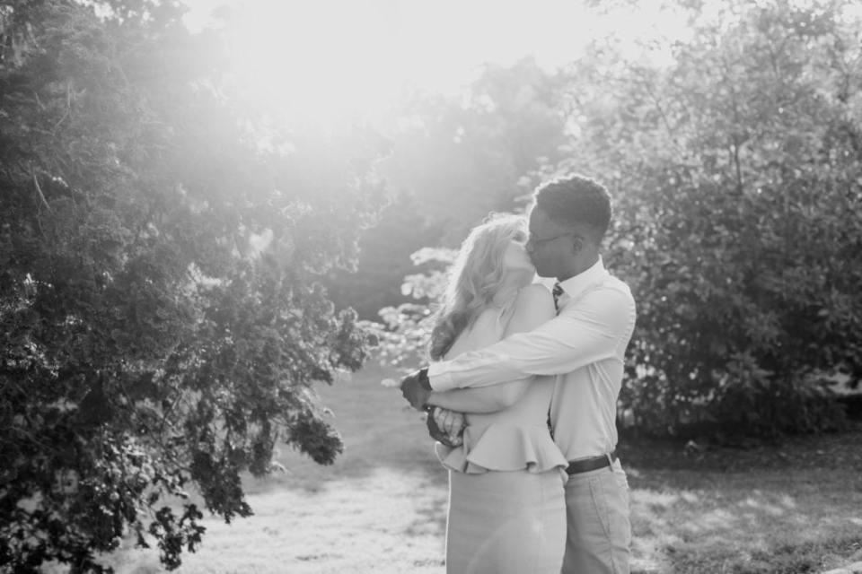 Black and white photo of engaged couple he standing behind her, arms wrapped around her, she with her head looking back at him, kissing.