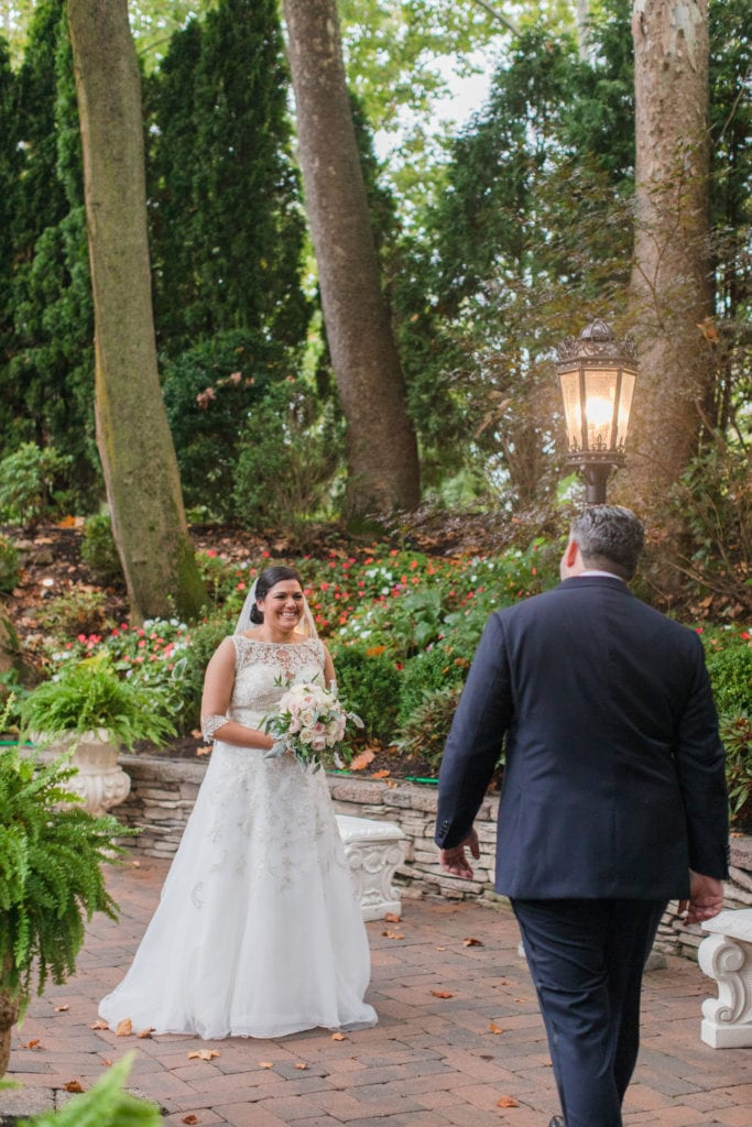 The bride smiling in her Stella York wedding gown as her groom walks towards her during the first look