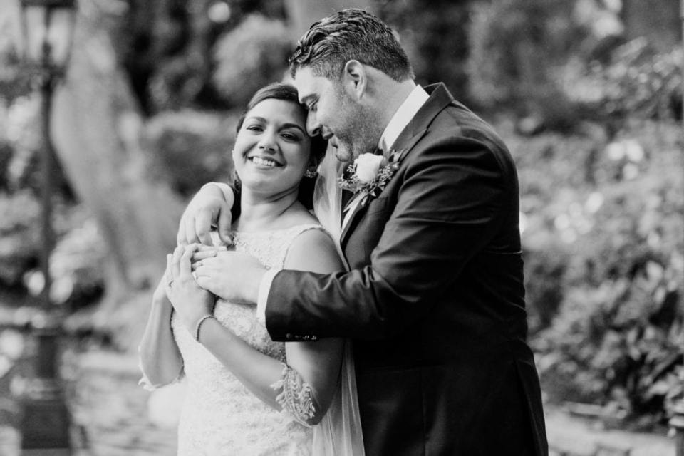 Black and white photo of the bride and groom from waist up, he behind her, arms wrapped around her.