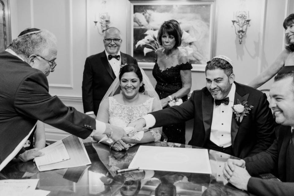 Black and white candid of the bride and groom, with their families, signing the ketubah