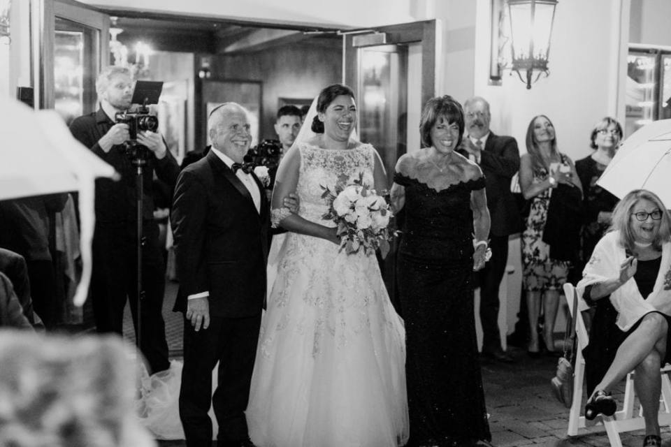 Black and white candid photo of the bride being walked down the aisle by her mother and father