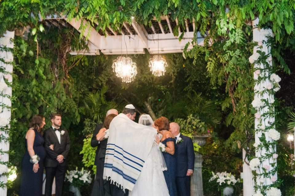 The bride and groom under the chuppah at Nanina's in the Park, while wrapped in a traditional prayer shawl