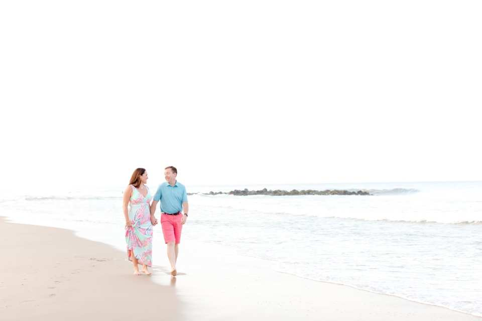 Engaged couple walks barefoot on the beach, hand in hand, looking at each other. She is wearing a maxi dress by Lilly Pulitzer, he is wearing a collared shirt and shorts by Vineyard Vines. On the beach in Spring Lake, N