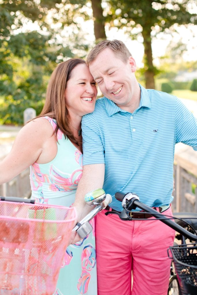 Bride and groom to be enjoying a laugh while standing with antique bikes in Spring Lake, NJ