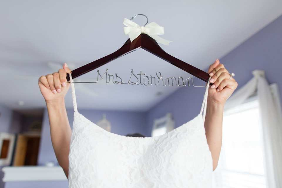 the bride holds her lace gown hanging on a custom wooden hanger with her new married name high above her head