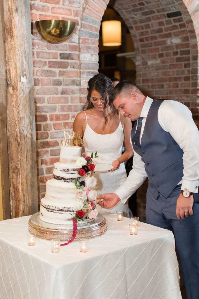 the bride and groom cut the four tier semi-naked cake with floral accents from Conroy Catering