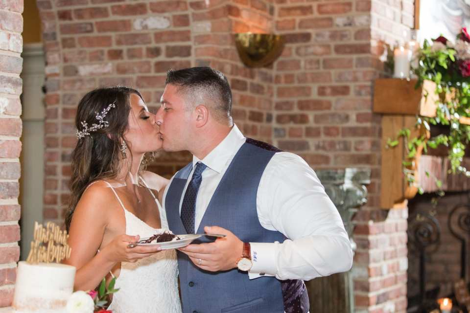 bride and groom share a kiss after the cutting of the cake