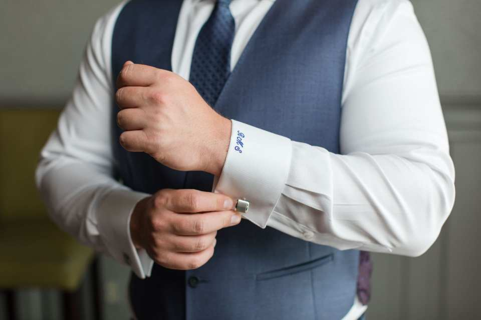 Close up of grooms custom shirt with embroidered cuffs and silver square cuff links