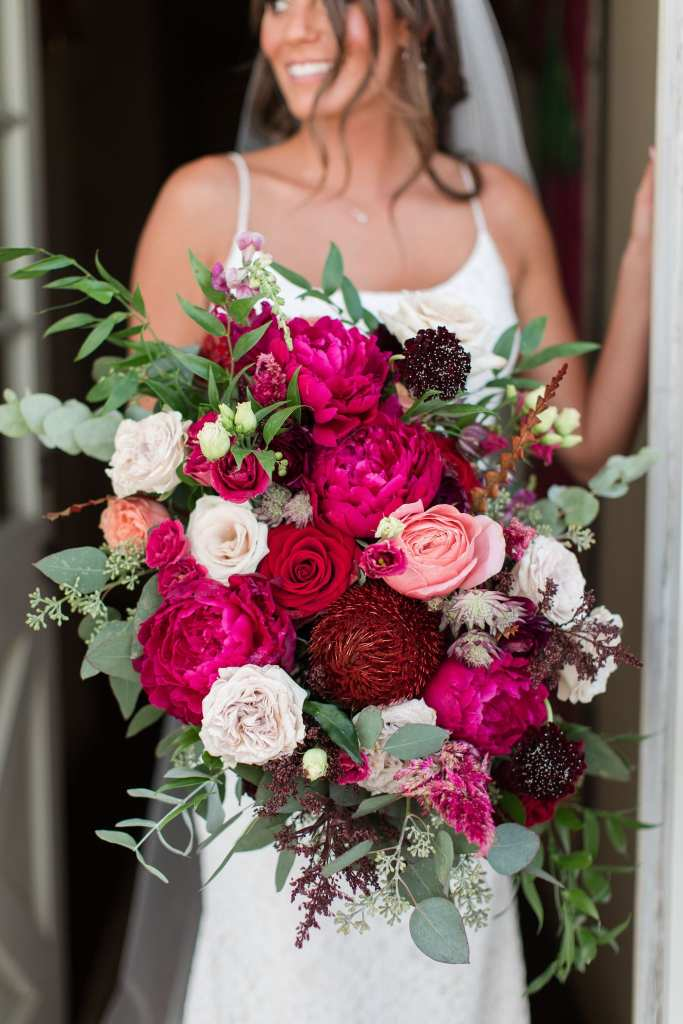 Bride holding her bridal bouquet by Ivy on Main consisting of various florals in shades of pinks, whites, and dark burgundy
