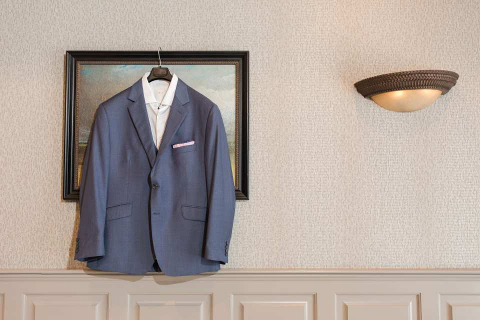 Custom suit by Generation Tux hung on display on picture frame