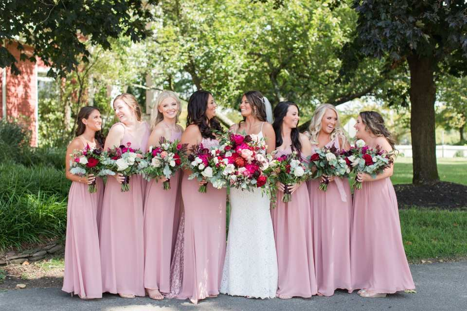 Formal photo of the bride in her gown by Mikaella with her bridal party in pink gowns by Azazie. Bouquets of various pinks, whites and greens by Ivy on Main