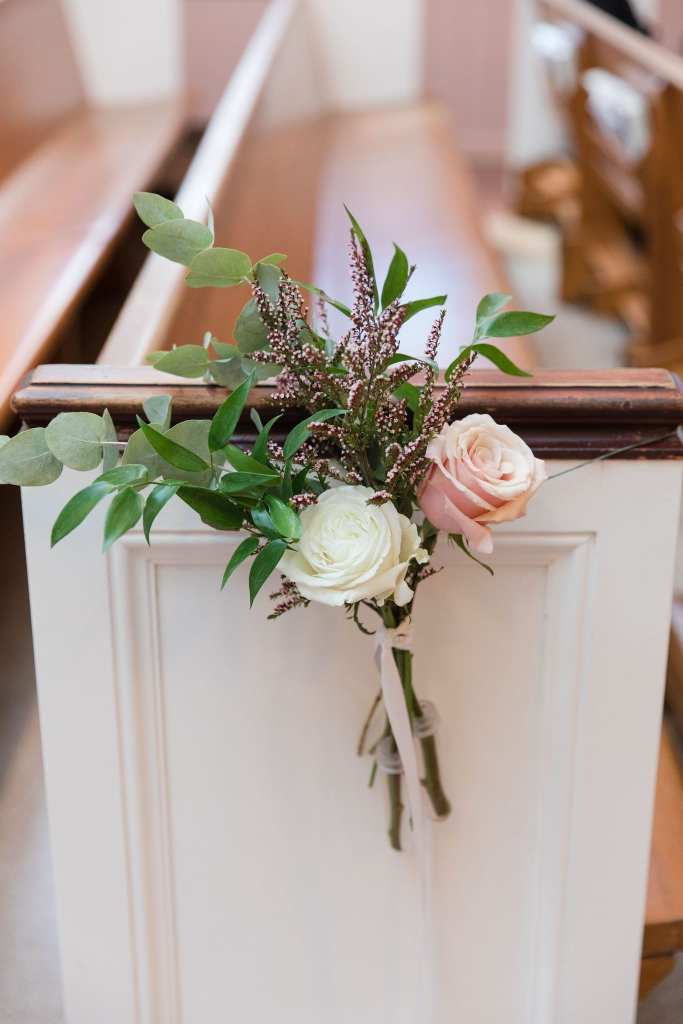 ceremony aisle decor of a light pink and cream rose, accented with wildflowers and greens by Ivy on Main