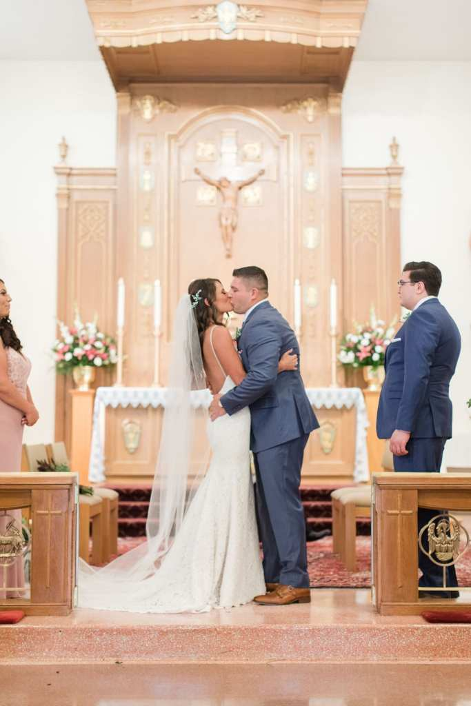 the bride and groom kiss for the first time as husband and wife on the altar of the church