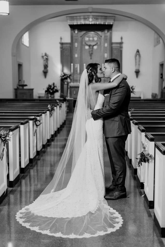 black and white photo of the bride and groom kissing down the aisle of the church