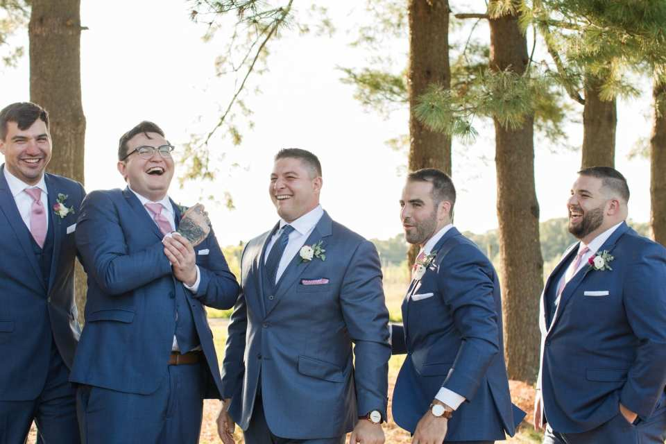 candid of the groom and his groomsmen in their blue Generation Tux suits with pink ties laughing with one another