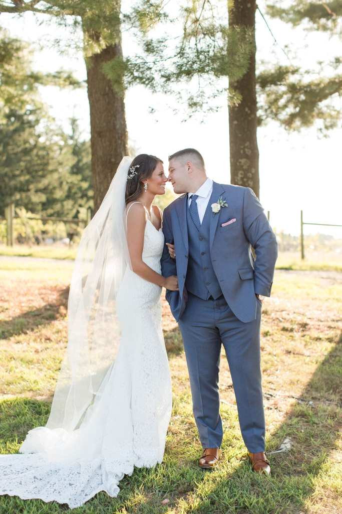 Bride and groom nose to nose while smiling outdoors