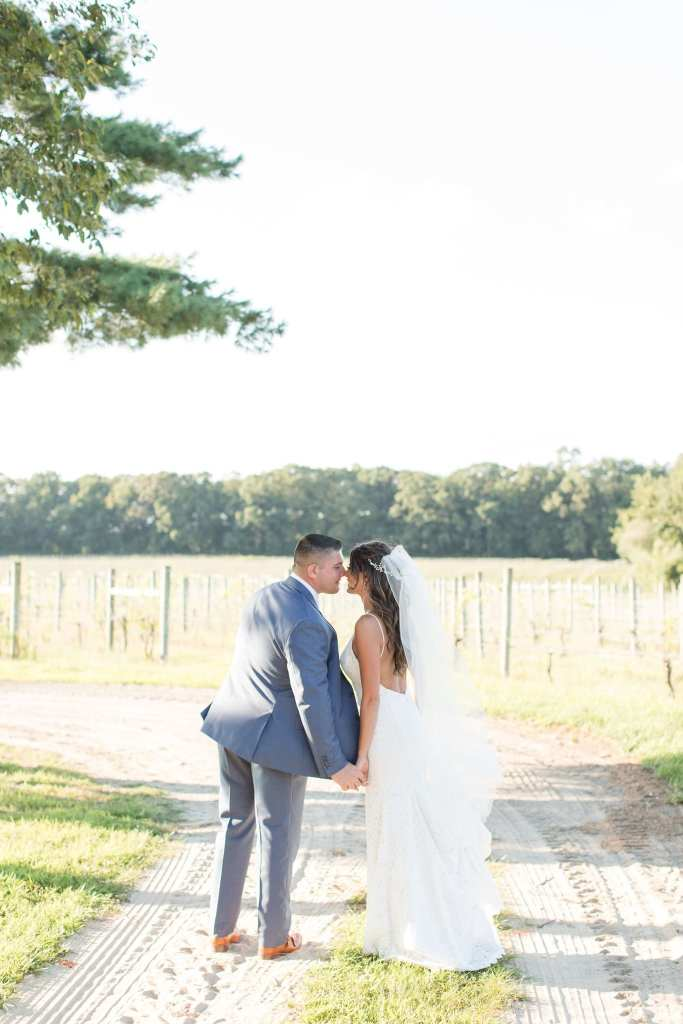 The bride and groom nose to nose amongst the vines at the vineyard at Laurita Winery by Jaye Kogut Photography