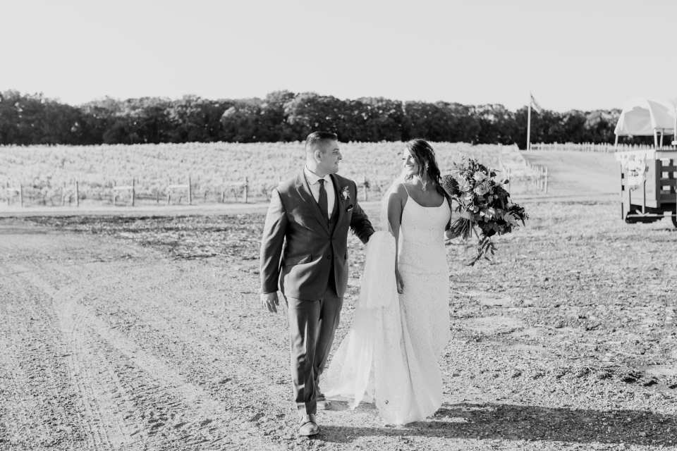 Black and white photo of the bride and groom walking around the vineyard at Laurita Winery