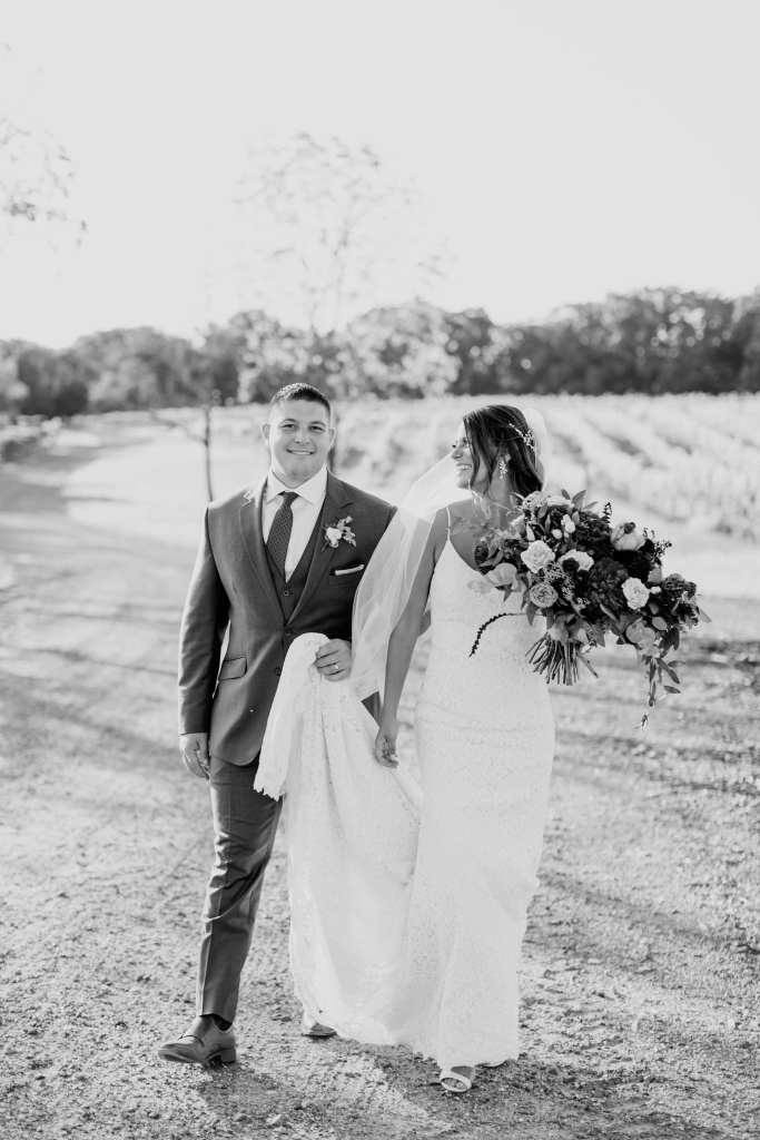 Black and white photo of the bride and groom walking through the vineyards at Laurita Winery