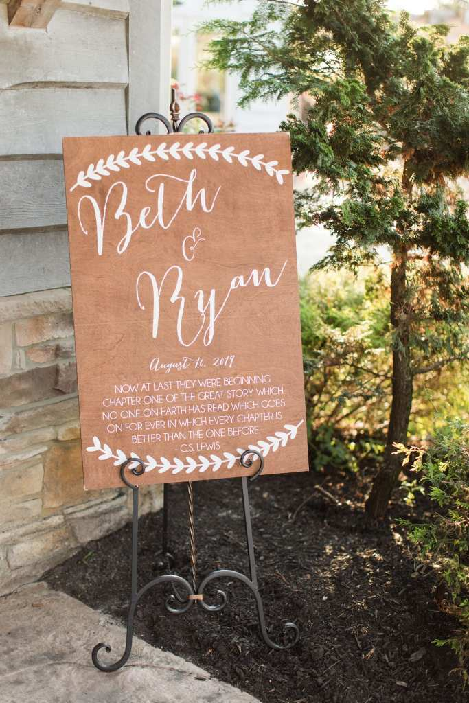 custom wooden signage welcoming guests to the wedding with a quote by C.S. Lewis